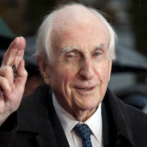 Barnboksförfattaren Michael Bond vinkar till fotografer på premiären till filmen Paddington.