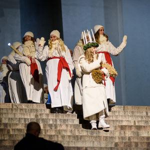 Lucia och tärnor går ned för Domkyrkans trappor.