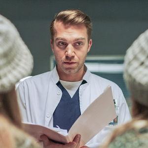Sairaalatakkinen mies katselee kahta samannäköistä henkilöä.