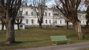 En bild på Lappvikens sjukhus med parkmiljö och en parkbänk