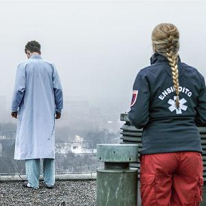 Sairaalasarjan ensihoidon työntekijä seuraa katon reunalla seisovaa potilasta.