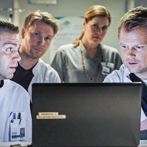 Syke-sairaalasarjan henkilökunta katsoo ruutua ja neuvottelee.