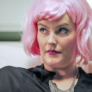 Nainen vaaleanpunaisessa peruukissaan.