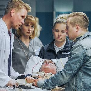 Sairaalasarja Sykkeen kohtauksesta: henkilökunta kuljettaa potilasta paareilla.