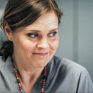 Nainen sairaalan hoitaja-asussa hymyilee jollekin.