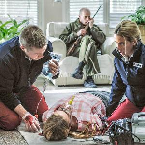 Sairaalasarjan ensihoitajat hoitavat lattialla makaavaa naista. Taustalla sohvalla istuu mies aseen kanssa.