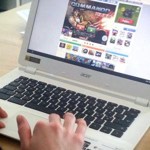 En pojke spelar dator.