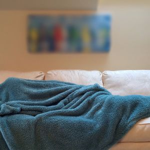 ihminen nukkuu sohvalla torkkupeiton alla piilossa