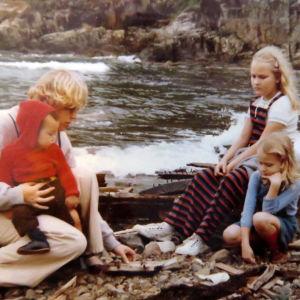 Kivikkoisella rannalla vaalea äiti kiinalaispoika sylissään ja isommat suomalais pikkutytöt istuvat kivellä ja katsovat mitä äidillä on kädessä