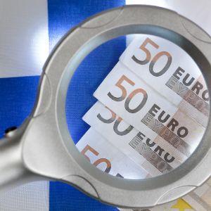 Bildsättning. Förstoringsglas över 50-eurossedlar, Finlands flagga i bakgrunden.