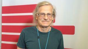 silmälasipäinen vaaleatukkainen mies hymyilee lievästi