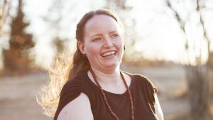 En leende Sara Snickars står med en korg i handen.
