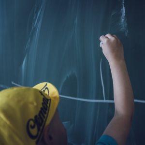 Barn skriver på krittavla