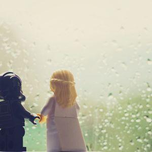 Legoukot hääparina sateisen ikkunan edessä