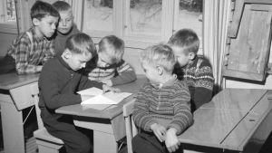 Pojat istuvat pulpeteissa, luokkatoverit katselevat yhden pojan saamaa kirjettä.