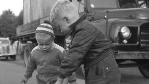 Pojat leikkivät jalkakäytävällä, takana kuorma-auto (orig. kuvasta rajautunut pois poikien leluauto)