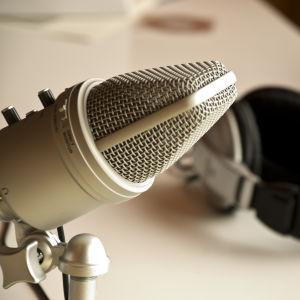 Mikroofoni, kuulokkeet pöydällä.