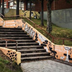 Portaat koulun seinän vierustalla ulkona, maalattu täyteen piirroksia ja lauseita eri kielillä.