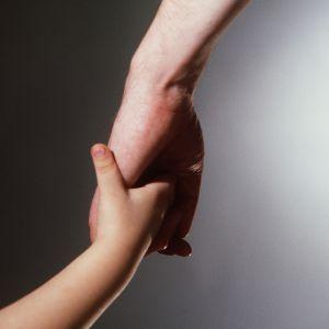 Barn och vuxen hand i hand.
