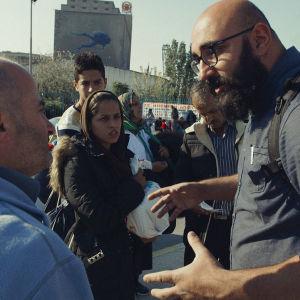 Ali Jahangiri turvapaikanhakijoiden joukossa keskustelemassa.