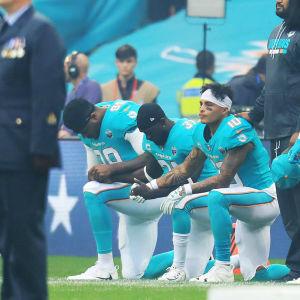 Miami Dolphins-spelare knäböjer.