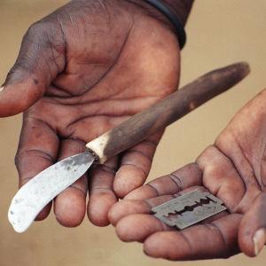 Hand med rakblad och trubbig kniv.