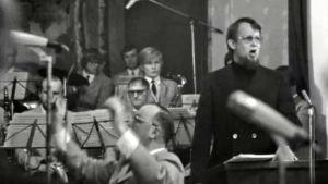 Kalle Holmberg johtaa Taistojen tiellä -laulun joukkoesitystä 1972