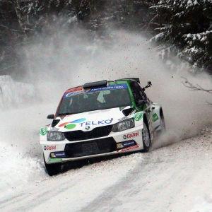 En rallybil kommer med hög hastighet i en kurva. Snön pyr.