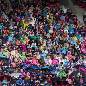 Skolelever i färggranna kläder på Ratina Stadion vid utlysningen av skolfreden