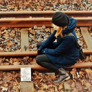 Nainen istuu junaraiteilla ja hänen edessää on Rosa Liksomin kirja Hytti nro 6.