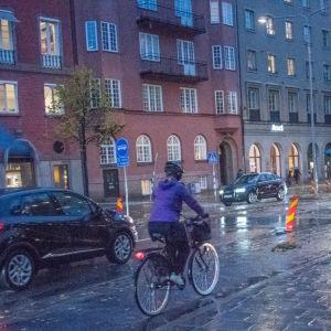En person cyklar i skymningen