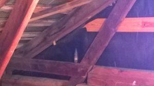 En granat syns inne i golvkonstruktioner av trä.