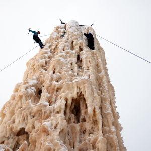 Jääkiipeilijä laskeutuu jäätornia alas köyden varassa.