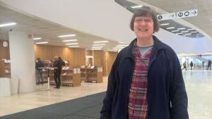 En kvinna står i biblioteket och ler mot kameran.