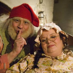 Tonttu Toljanteri (Kunto Ojansivu, vas.) saa muhkean joulu-urakan, kun hänen pitää käydä unipöpön saaneen muorin (Satu Säävälä, oik.) hommiin Tonttu Toljanteri muorin töissä -joulukalenterisarjassa vuodelta 2007.