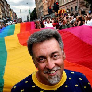 Gilbert Baker står framför en 250 meter lång regnbågsflagga på Prideparaden i Stockholm år 2003.
