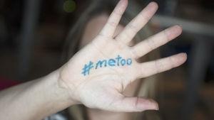 Kvinna håller upp sin hand där det står #metoo.