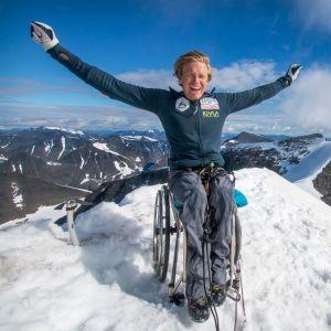 Aron Anderson i rullstol, på toppen av Kebnekaise. Bergskammar syns i bakgrunden.