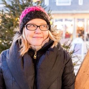 Soile Suvanto seisoo Oulun Rotuaarilla kuusien katveessa.