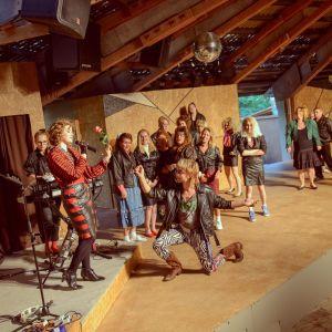 """Doris (Mecki Ruokolahti) står på scen med bandet The Blizzard under pjäsen """"Doris, flickan i läderrock""""."""