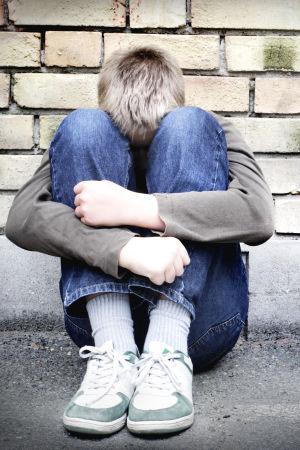 En pojke sitter med huvudet i famnen.