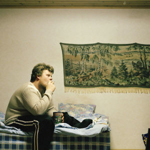 Mies istuu sängyllä ja katsoo telkkaria.