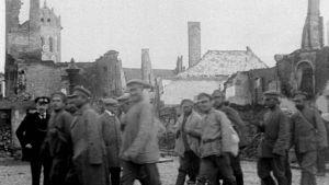 sotilaita ja raunioita taustalla