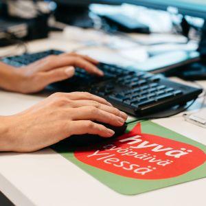 Kädet tietokoneen näppäimistöllä, hiirimatossa lukee Hyvä työpäivä Ylessä