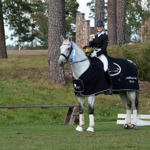 Dressyrryttaren Jenni Rintala sitter iförd dressyrdräkt på sin häst Nk Unique. Fotot är taget utomhus.