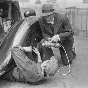 Radioreporter Alexis af Enehjelm intervjuar en man som fixar en bil, 1930-tal