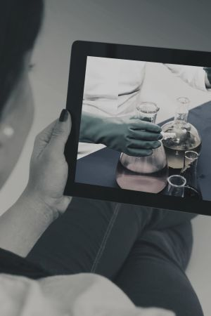 Kvinna håller i en ipad och tittar på skärmen där det finns ett kemiskt laboratorium.