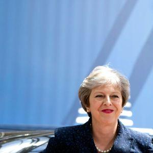 STheresa May med en EU-flagga bakom sig