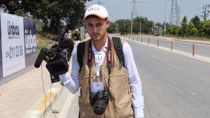 En ung man med kamera och filmkamera. Står på en gata med reklamskyltar och elstolpar i bakgrunden. Soligt väder.
