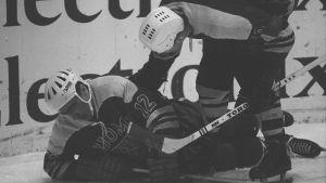 Suomen pelaaja kaatuneena maassa vanhassa mustavalkoisessa kuvassa.